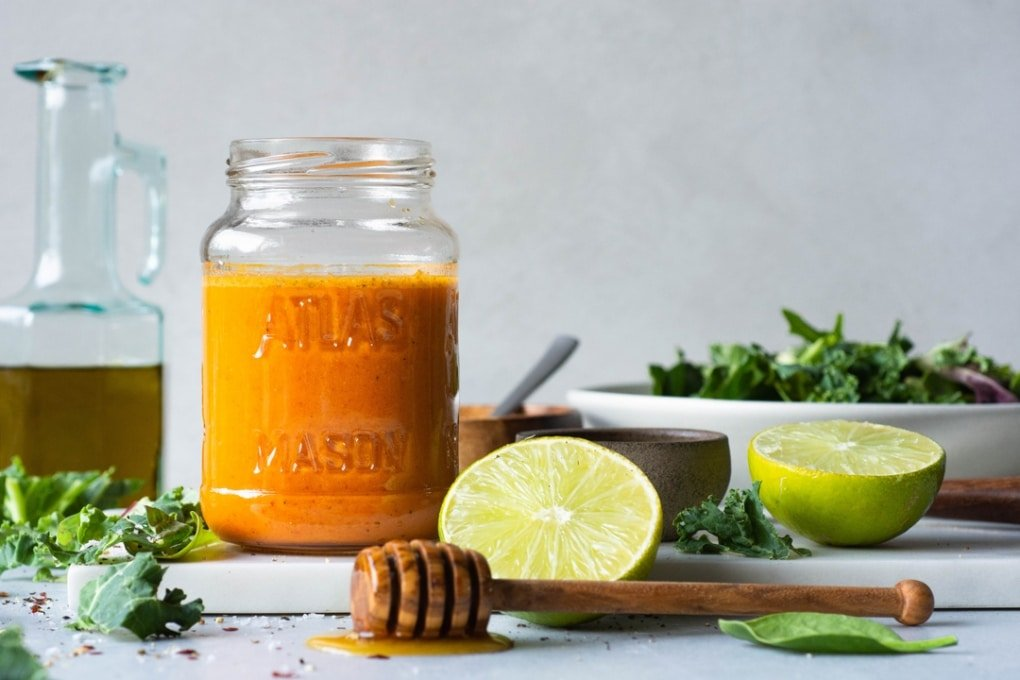Side view of a jar of bright orange roasted red pepper dressing next to a cut lime and a bowl of salad greens