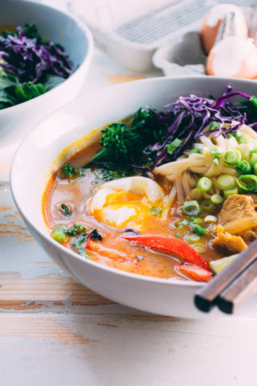 a satisfying and easy curry noodle soup made with chicken, udon noodles, red curry paste, garlic, ginger, turmeric, onions, red peppers, broccolini, soft boiled eggs and finished with cilantro, green onions and shredded red cabbage. | www.nyssaskitchen.com