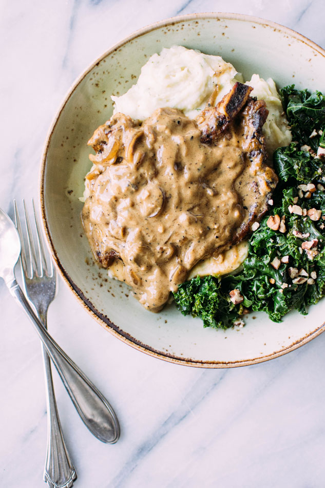 Caramelized onion smothered pork chops with herb whipped parsnips and kale are here to take your gluten free // paleo dinner to the next level of comfort + satisfaction! Nestled in a creamy dairy free sauce these pork chops pair perfectly with dreamy whipped parsnips and bright and nourishing kale for the perfect comfort food meal.
