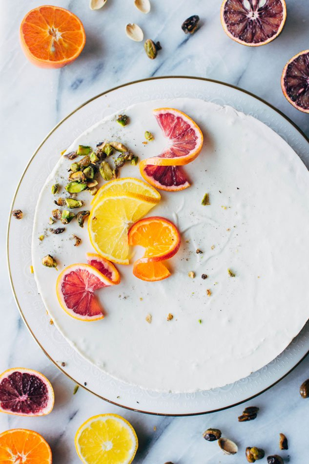 Blood orange and cardamom pistachio no bake greek yogurt cheesecake! A delightful + healthy gluten free dessert that will satisfy your cheesecake loving sweet tooth. Made with greek yogurt, coconut, blood oranges, vanilla, a date-sweetened pistachio crust and topped with fresh citrus and cardamom candied pistachios.