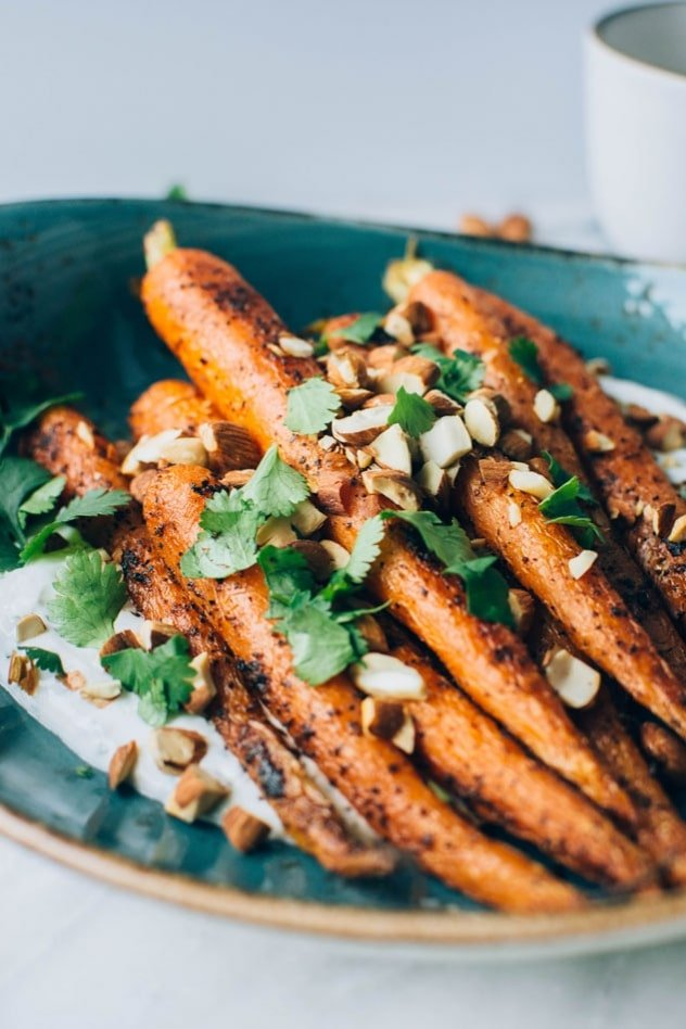 Black pepper roasted carrots with savory cilantro yogurt and roasted almonds are super easy and flavor packed to the max! The carrots are seasoned with black pepper, a little bit of paprika, and paired with a bright + savory cilantro yogurt sauce - the perfect combo! Topped with some roasted almonds to add some texture and crunch for the win!