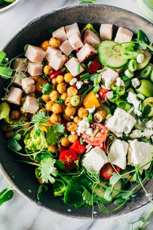 Loaded greek salad bowl with crispy chickpeas and creamy jalepeño dressing is satisfying, healthy and easy to make! Packed with crisp greens, loads of veggies, buttery casteltravano olives, crispy chickpeas and feta cheese it's a salad lovers DREAM!