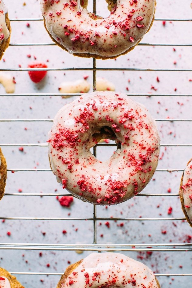 Grain free raspberry donuts with a vanilla coconut glaze! Crumbly in all the right ways, slightly springy in texture, studded with fresh raspberries, dipped in a luscious vanilla coconut glaze and sprinkled with tart dried raspberries.