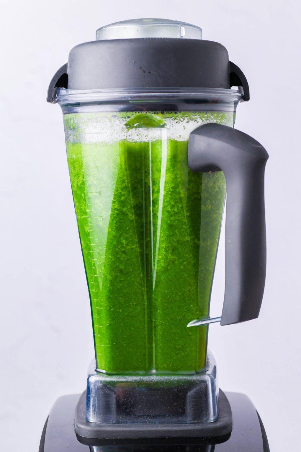 Straight on shot of a bright green blended green juice in a Vitamix blender. In front of a white background.