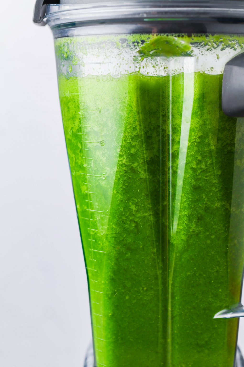 Straight on shot of pouring green juice in a small glass - on a white background.