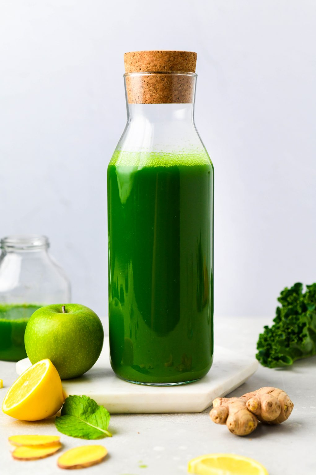 Straight on shot of a carafe filled with green juice. On a light background surrounded by a green apple, a sliced lemon, ginger, fresh mint, and a few kale leaves.