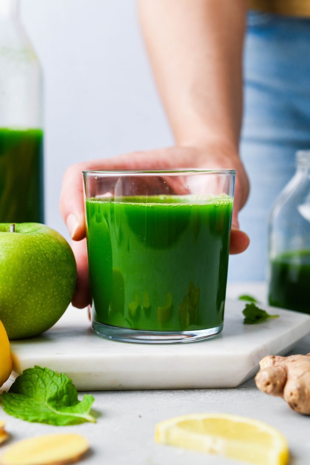 Straight on shot of a hand holding a small glass of green juice. On a light background surrounded by a green apple, a sliced lemon, ginger, fresh mint, and a few kale leaves.