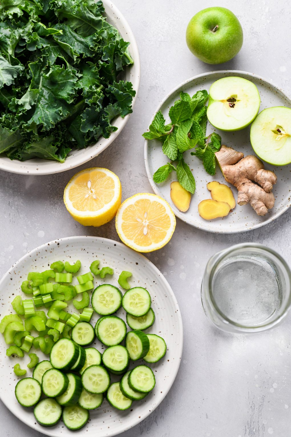 Overhead shot of the various ingredients used to make green juice in a blender. A Large white speckled bowl filled with kale leaves, a small plate with a cut apple, fresh mint, cut ginger, a lemon cut in half, another plate with sliced celery, sliced cucumber, and a mason jar with water. On a light grey background.