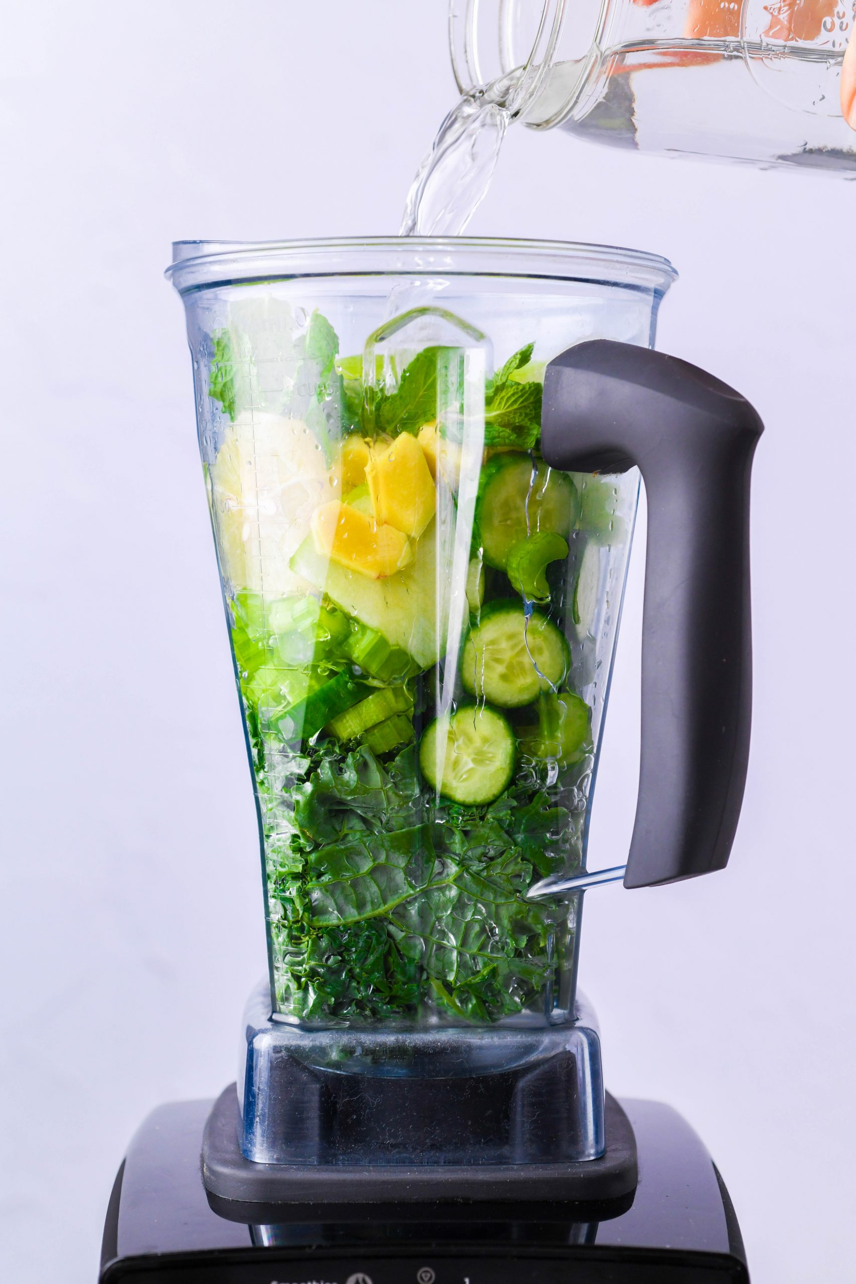 Image of pouring blended green juice into a strainer positioned over a large bowl to strain out the solids.
