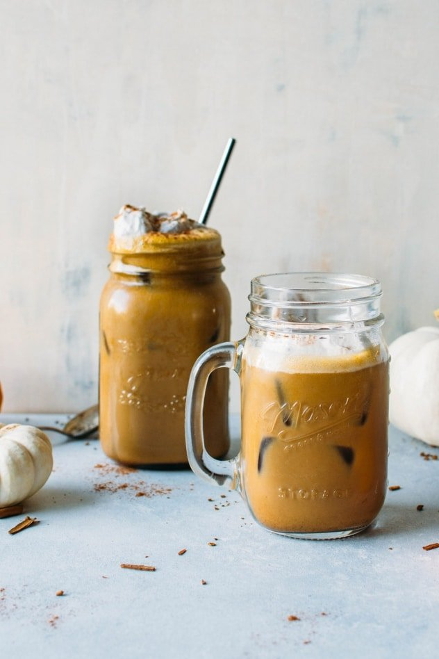 Paleo iced pumpkin spice latte - a dairy free and healthier version of everyone's favorite seasonal drink! Made with real pumpkin and sweetened with maple syrup. Top with coconut whipped cream for the ultimate treat!