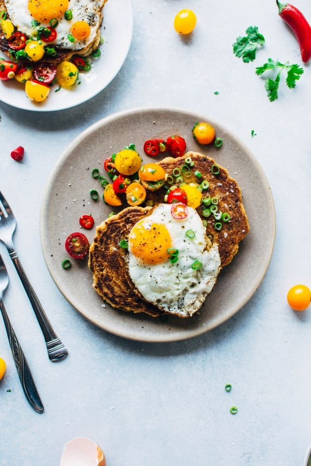 A crazy easy and delicious recipe for savory breakfast pancakes! Made with crumbled bacon, green onions, and topped with a tomato jalapeño salad and fried eggs, these pancakes are the perfect reason to stay home and cook breakfast this weekend!
