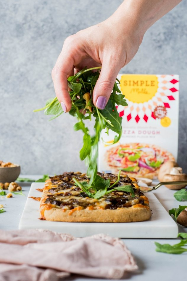 This grain free caramelized onion and mushroom pizza with arugula is made with Simple Mills almond flour pizza dough, topped with flavorful caramelized onions and mushrooms, smoked mozzarella cheese, and a peppery + bright arugula and toasted walnut salad - basically making it the ideal healthy pizza situation!