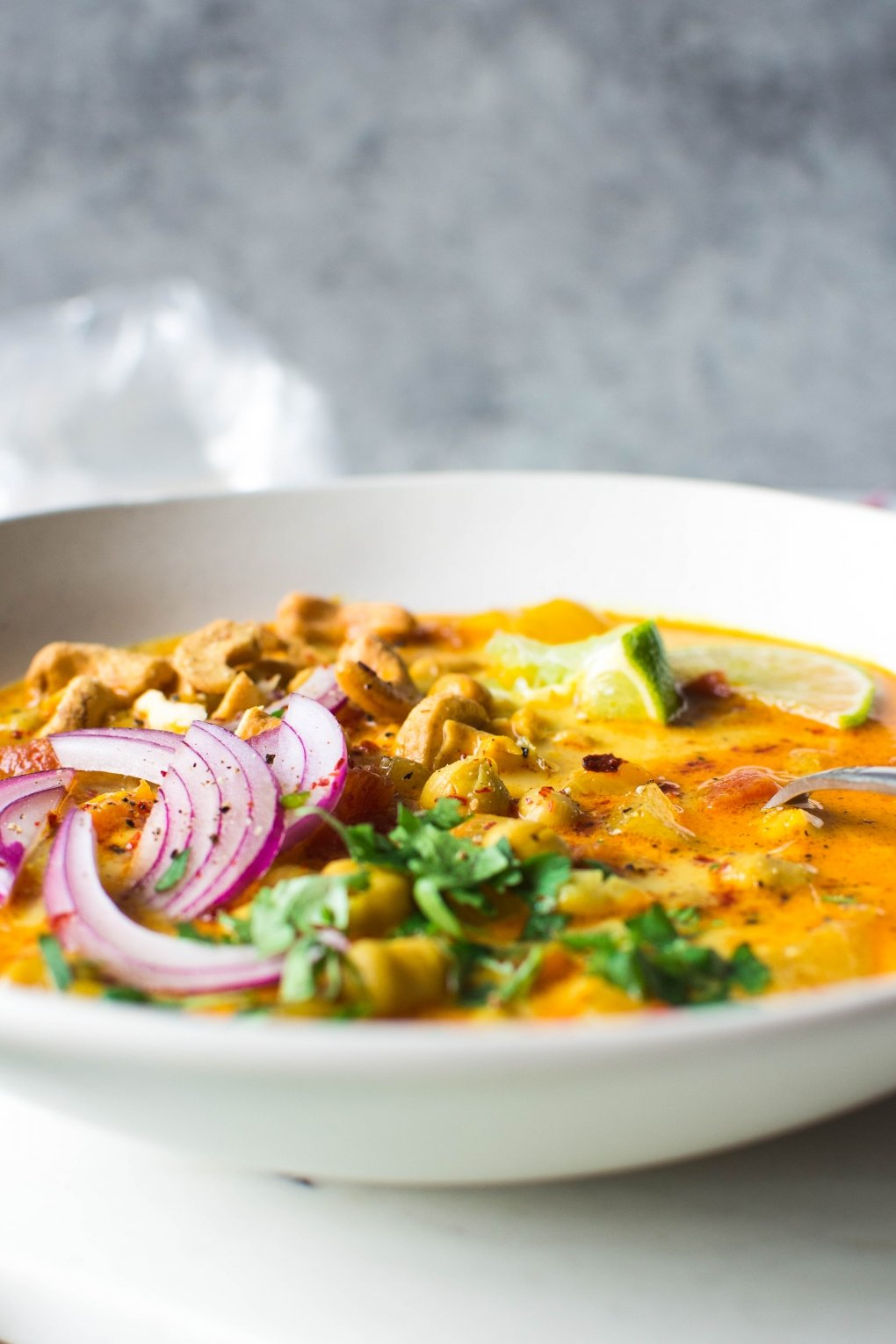Close up and side angle shot of a large white bowl of bright orange chickpea and tomato coconut curry soup. Soup is topped with fresh red onion slices, chopped herbs, curry spiced cashews, and lime wedges. On a white background next to scattered herbs, lime wedges, and cashew bits.
