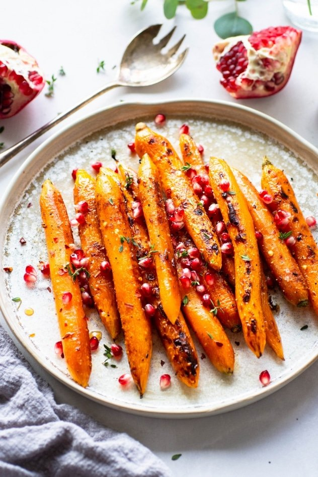 These maple chili glazed carrots with thyme and pomegranate are an easy and delicious side dish for your holiday table. Paleo, vegan and oh-so-yummy! Savory and sweet - loaded up with fresh and bright pomegranate seeds to delight your taste buds!