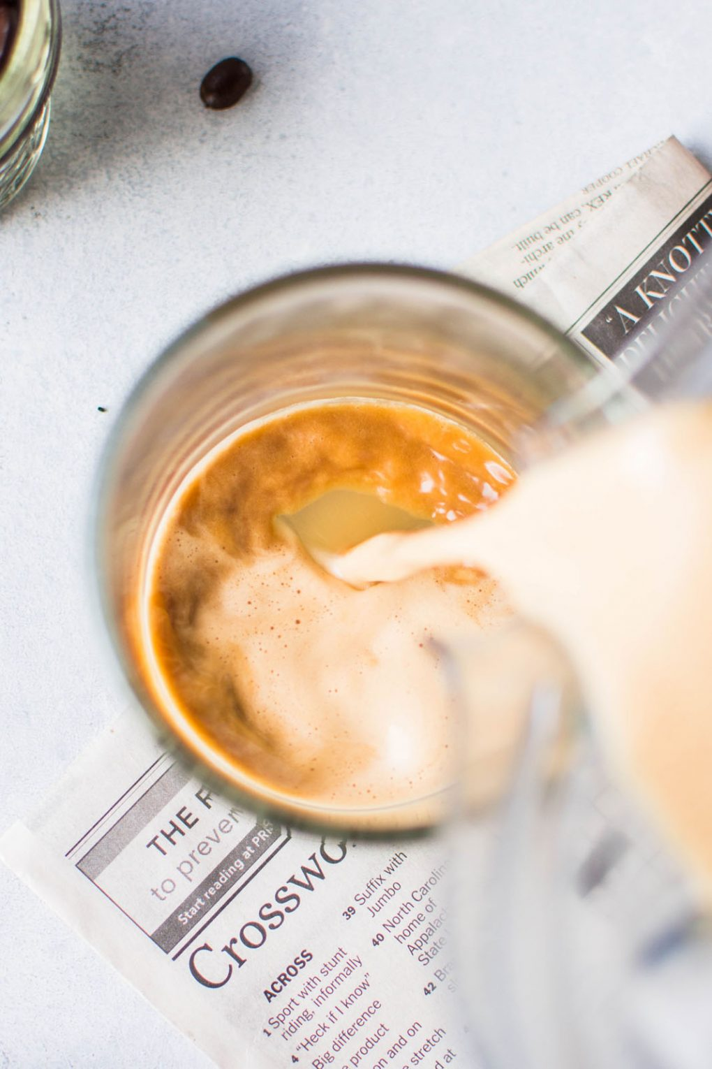Overhead shot of a blender pouring creamy bulletproof coffee into a glass mug. On a light colored background.
