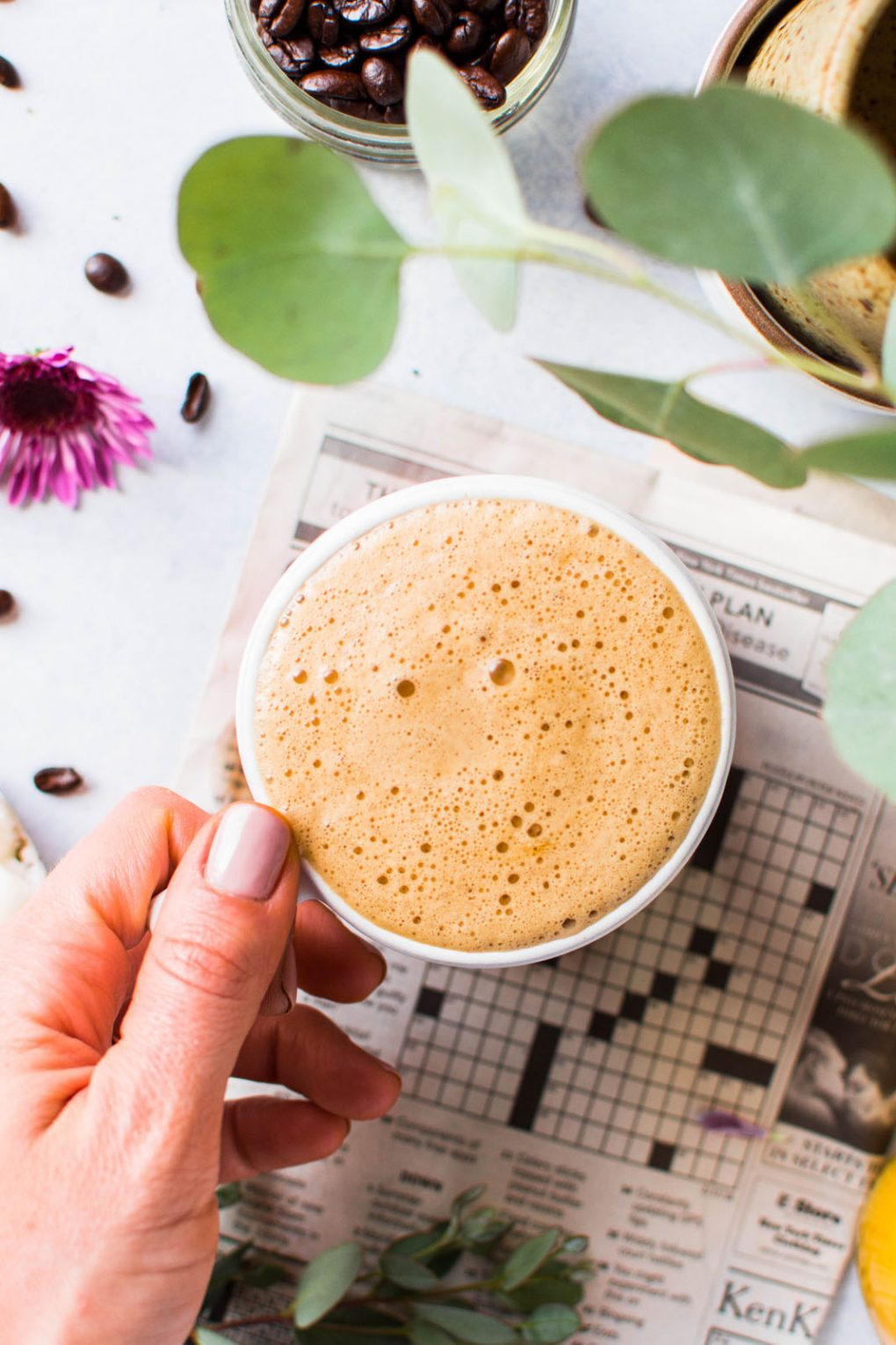 Overhead shot of a hand holding a super creamy cup of bulletproof coffee for a how to make bulletproof coffee in 3 easy steps guide. On a light background with a newspaper crossword puzzle peeking into the frame.