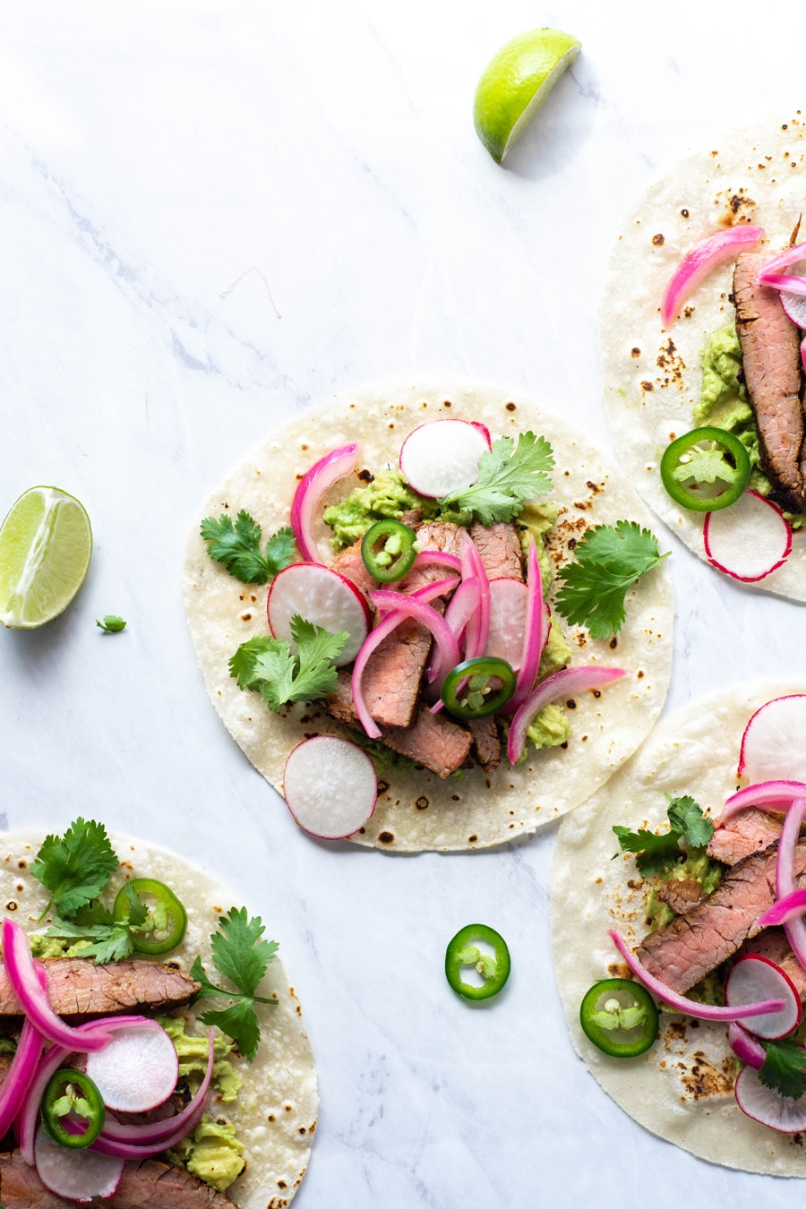 Multiple steak tacos on a white background with cilantro, thinly sliced jalapeno, pickled red onions