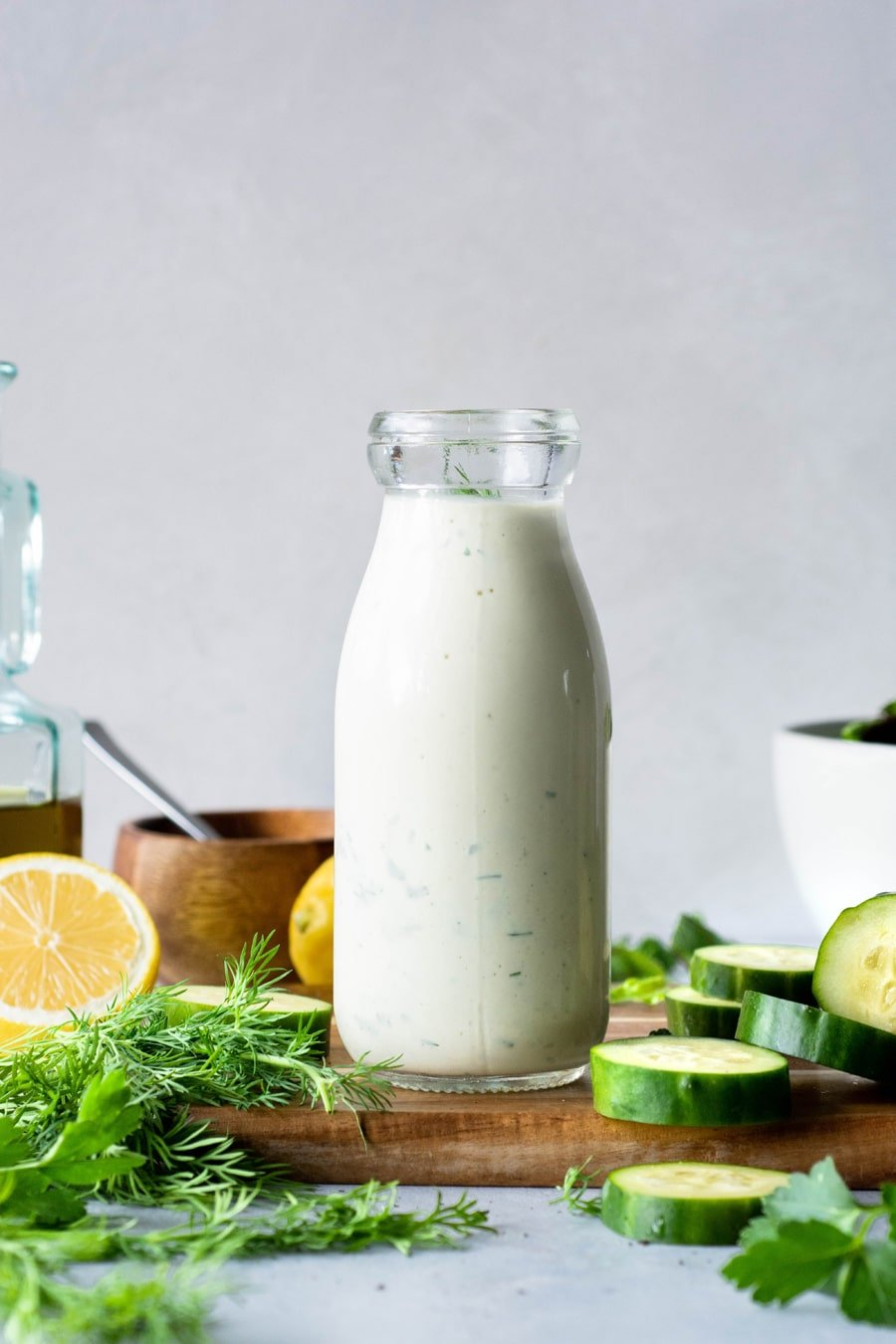 Straight on view of a jar of homemade dairy free ranch with lemon, herbs, and cucumbers on a wooden board