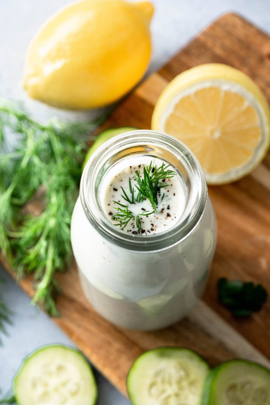 45 degree angle view of a jar of homemade dairy free ranch with herbs and cucumbers on a wooden board