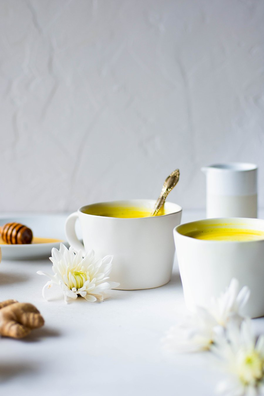 Side angle of two bright yellow golden milk latte in a white mug on a light grey background with white flowers and ginger