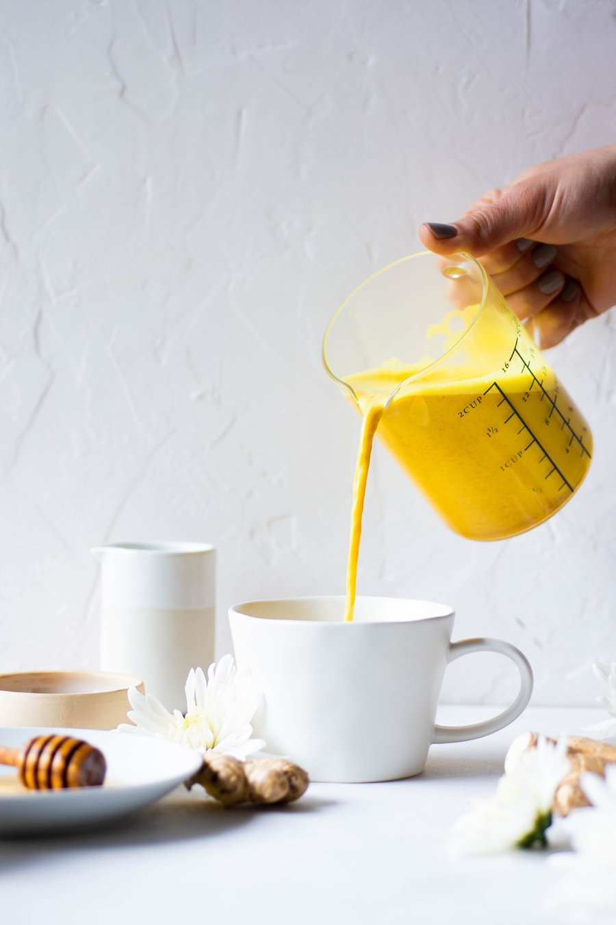 Pouring a bright yellow golden milk latte into a white mug with a white background