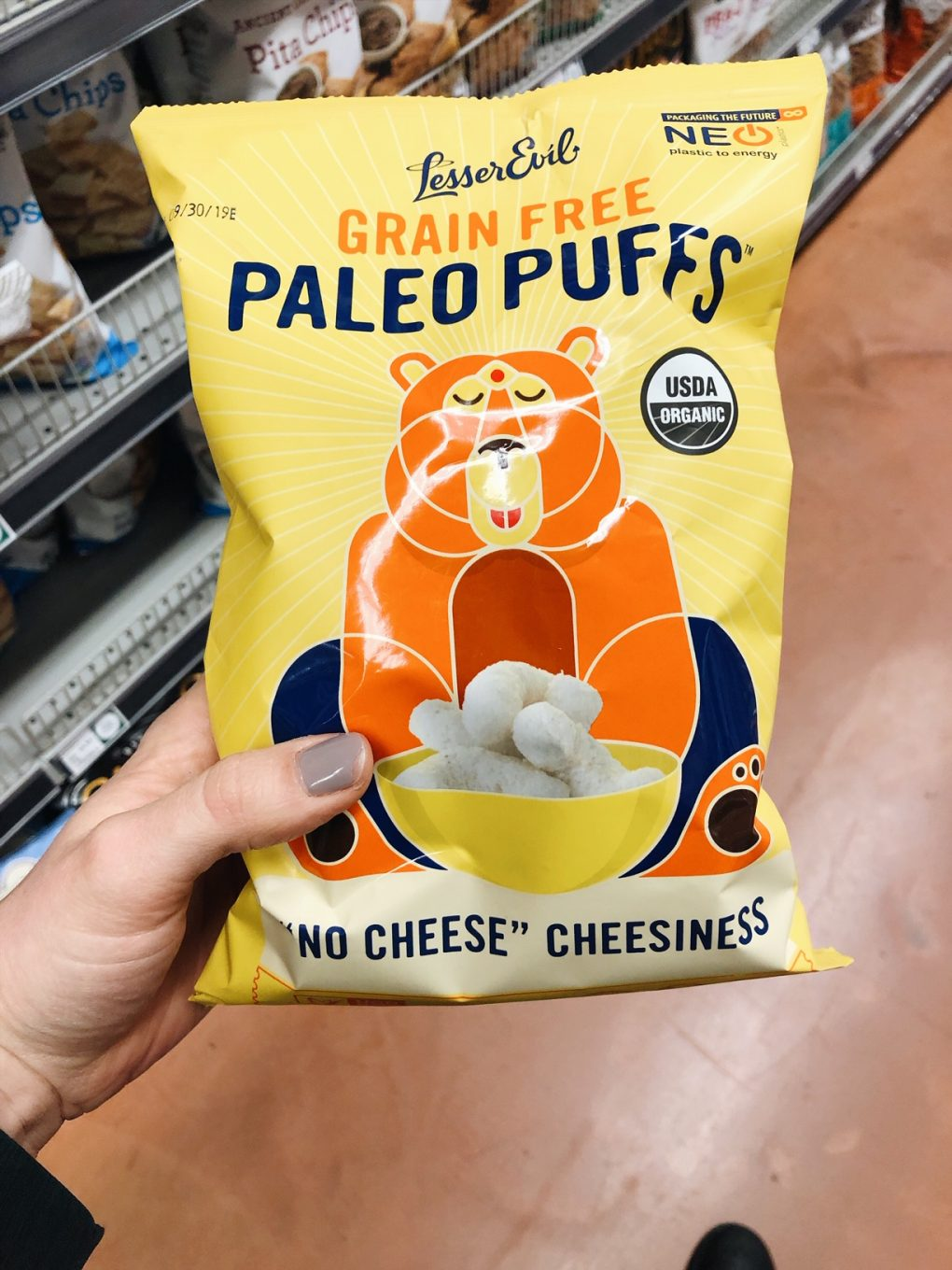 "Holding a bag of Lesser Evil Grain Free Paleo ""cheese"" puffs in the grocery store"