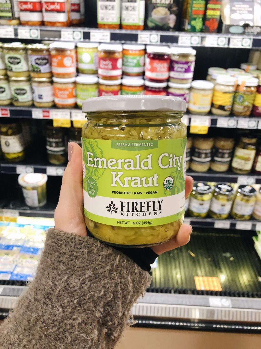 Holding a jar of emerald city sauerkraut at the grocery store