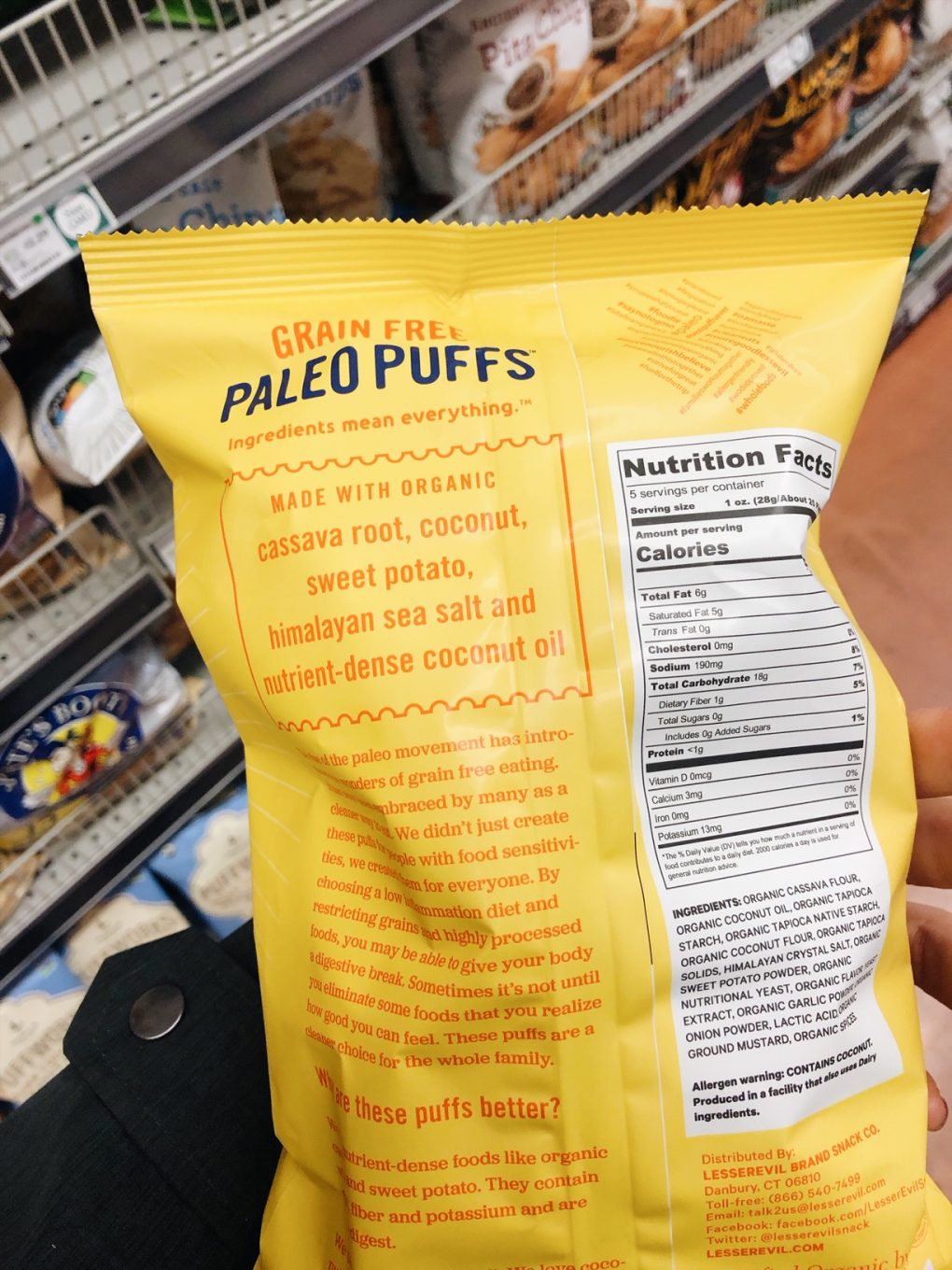 "Holding a bag of Lesser Evil Grain Free Paleo ""cheese"" puffs in the grocery store with ingredients showing"