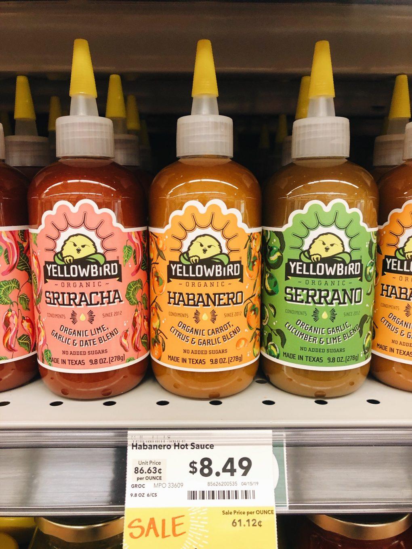 Three types of yellow bird hot sauces on a shelf at Whole Foods - Sriracha, Habañero, and Serrano