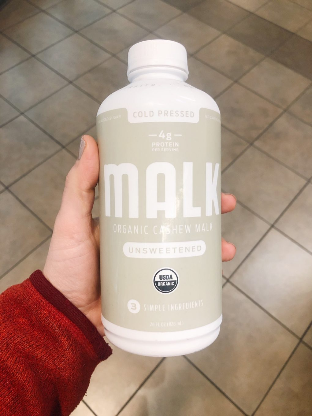Holding a bottle of malk organics white label cashew milk in the grocery store