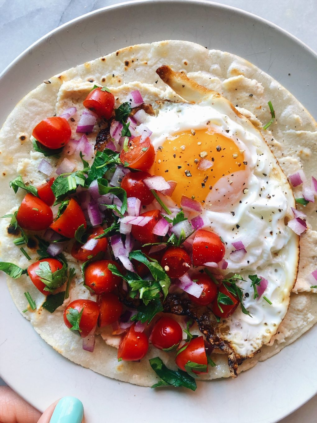 An open faced Mediterranean breakfast taco with a fried egg and tomato + herb salad held by a left hand with teal fingernails on a white plate and white background