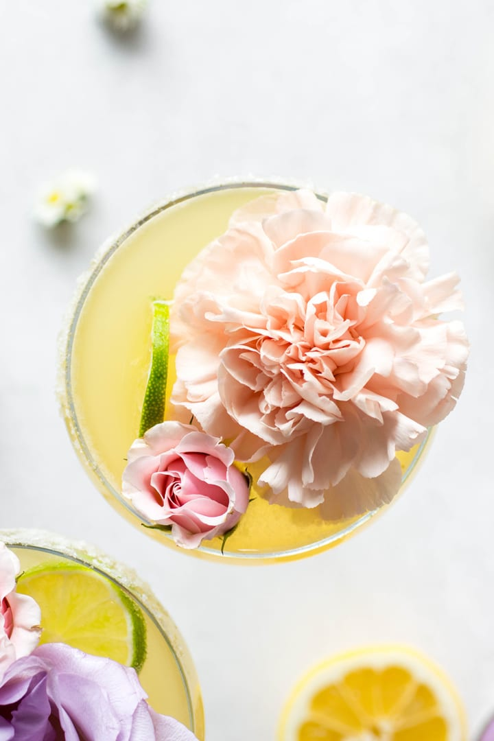 An overhead view of a bright yellow kombucha margarita served up with a big pink flower and a lime wheel.