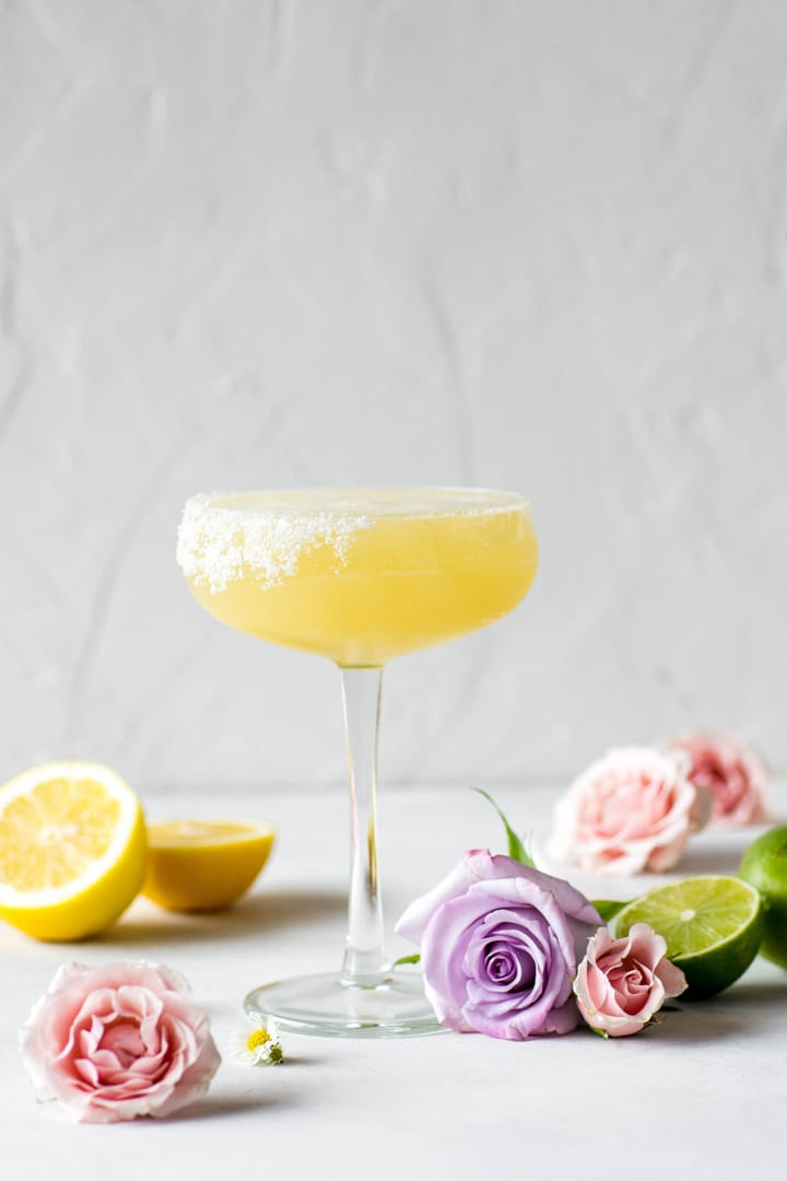 An side view of a bright yellow kombucha margarita served up with a big pink flower and a lime wheel.