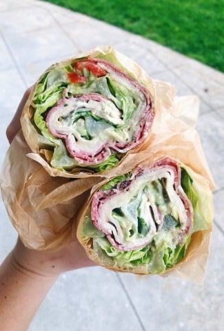 Lettuce wrapped sandwich cut open with turkey, salami, avocado, tomato, and mustard + mayo