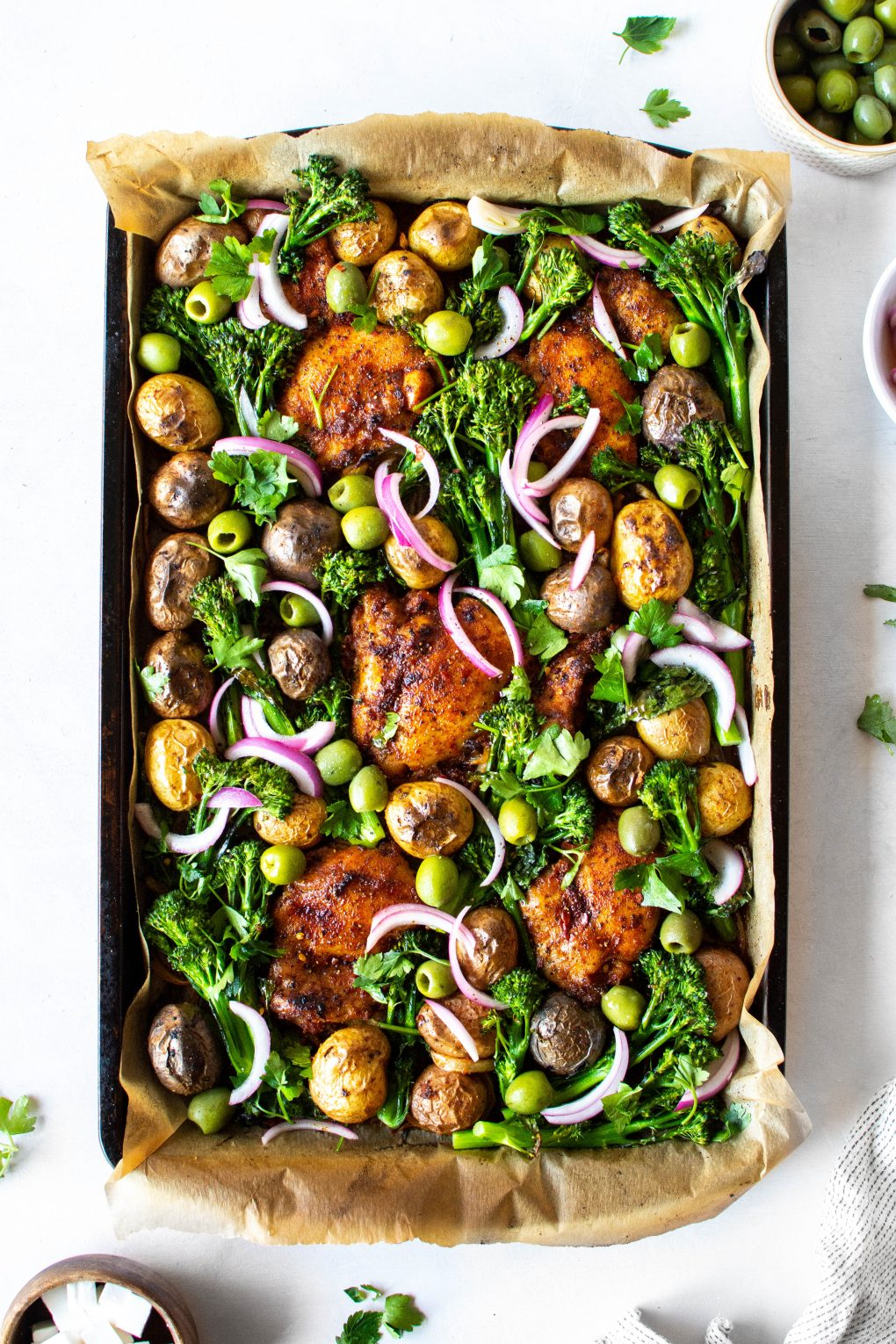 An overhead view of a roasting tray with spiced chicken thighs, potatos, broccolini, olives, and pickled red onions on a white background