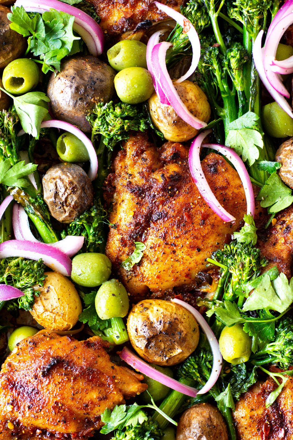 Overhead view of of a roasting tray with spiced chicken thighs, potatos, broccolini, olives, and pickled red onions