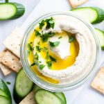Small glass jar with swirled cauliflower hummus. Topped with olive oil and parsley, on a white background and surrounded by crackers and cucumber slices