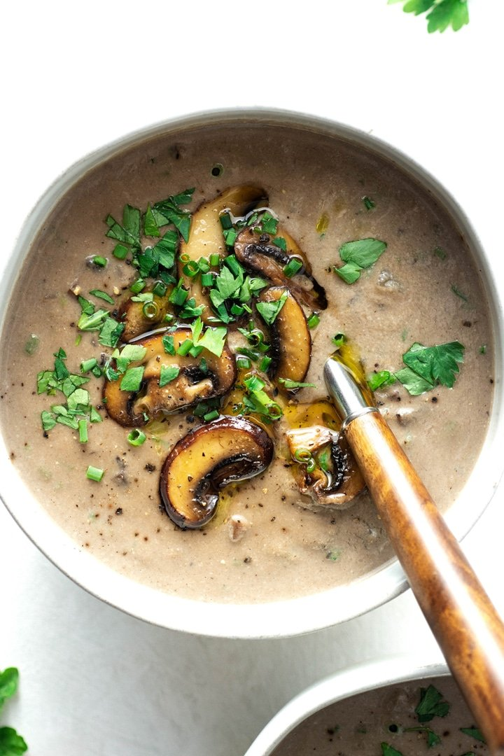Bowl of cream of mushroom soup topped with sauteed mushrooms, fresh green herbs, with a spoon lifting out some soup on the right side of the bowl on a white background