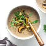 Overhead view of cream of mushroom soup with some sauteed mushrooms and fresh green herbs on top.