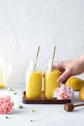 Hand in the right frame of the picture grabbing one of two side by side golden mango lassi's in smoothie jars against a white back drop