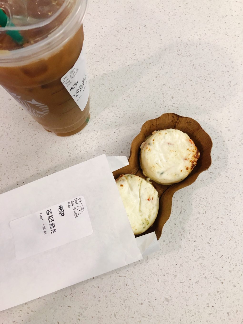 Starbucks sous vide egg white bites partially out of the package on a white background next to a venti iced coffee