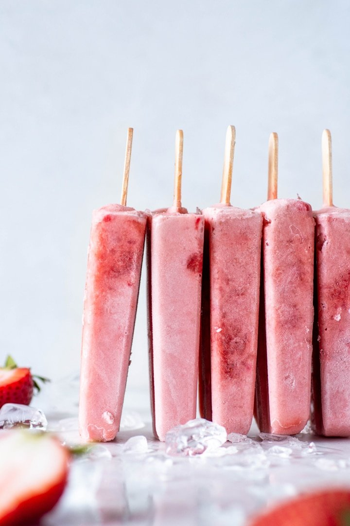 A row of pink strawberry popsicles standing up leaning against each other against a white back drop
