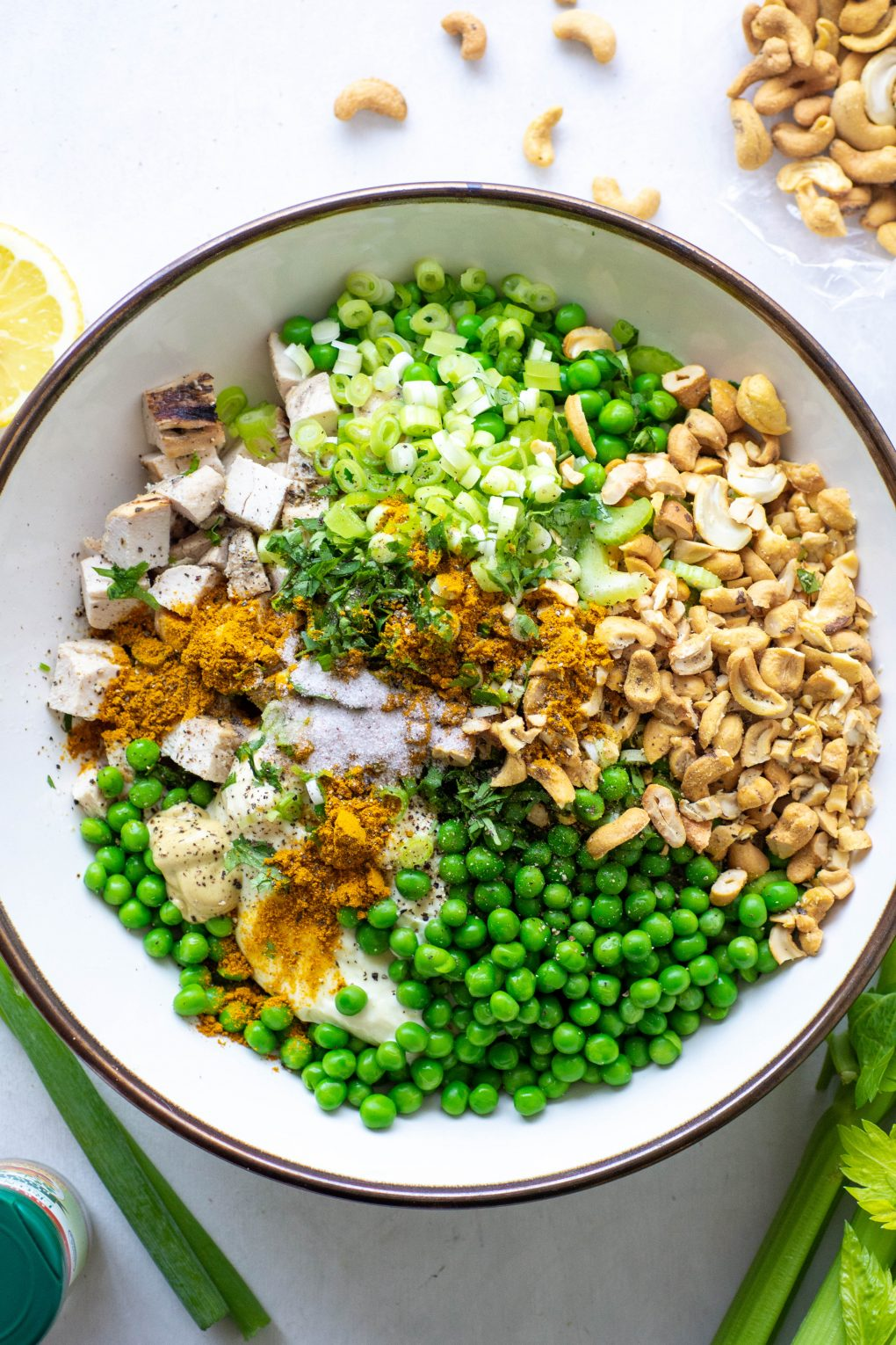 Overhead view of a bowl filled with curried chicken salad ingredients - chopped chicken, green peas, celery, green onions, cashews, mayo, and spices.