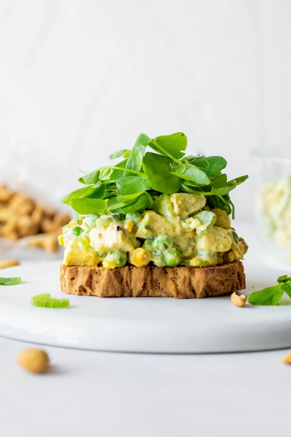 Close up side view of an open faced chicken curry salad sandwich with bright greens on a white background.