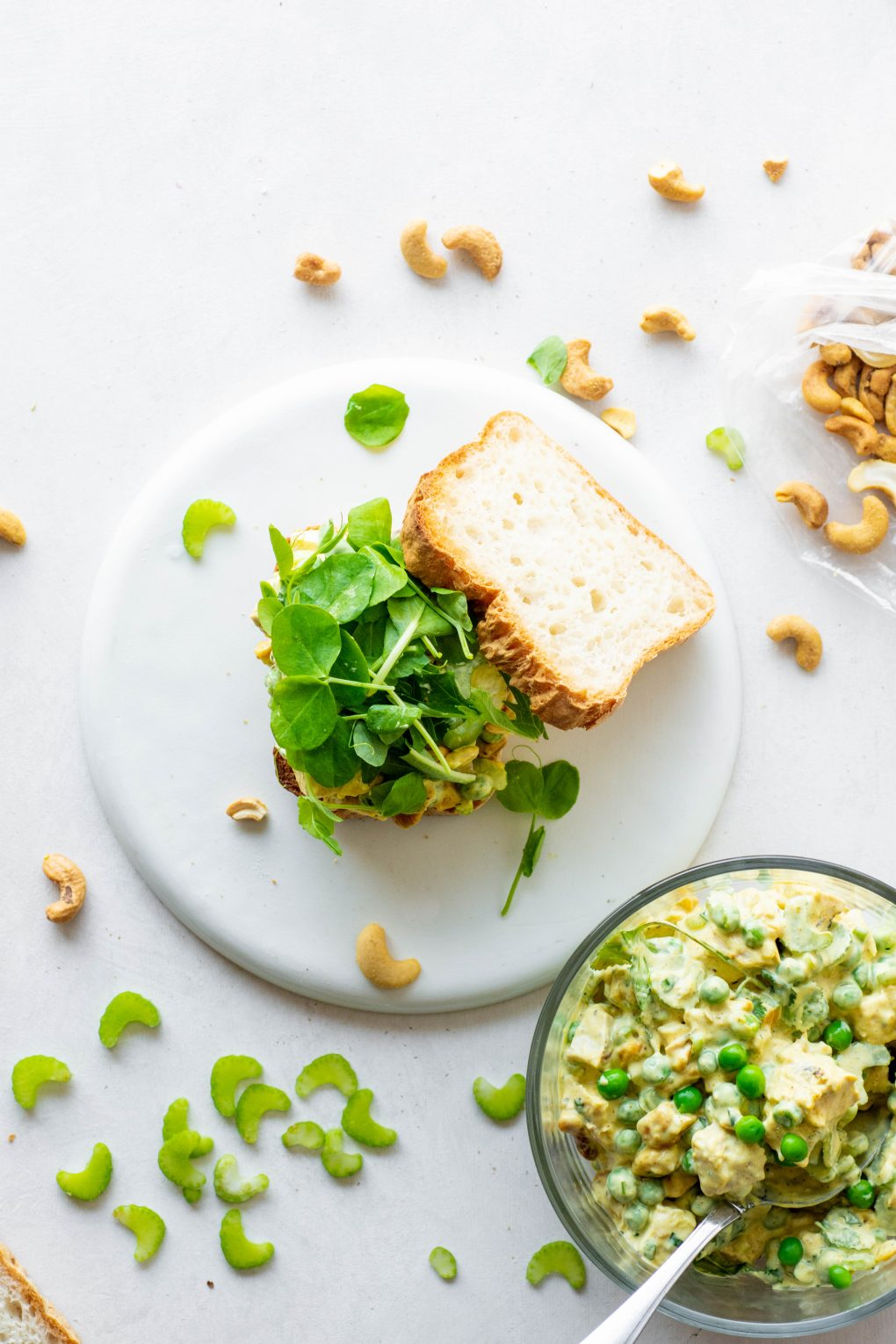 Overhead shot of an open faced chicken curry salad sandwich topped with salad greens on a white background. Surrounded by a bowl of chicken salad, some toasted cashews, and sliced celery.