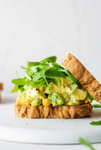 Side view of a curried chicken salad sandwich with some fresh greens and the top piece of bread angled off to the side. On a white background.