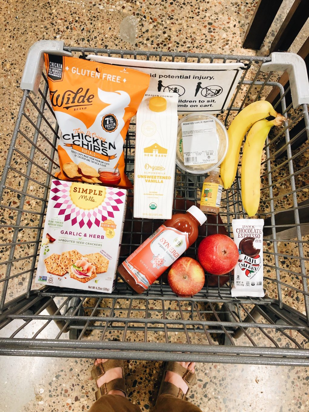 Overhead view of a grocery cart with snacks, fruit, kombucha, almond milk, and chocolate