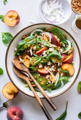 A large bowl filled with green salad with peaches, chopped almonds, sliced onion, and crumbled feta cheese with mustard dressing. Surrounded by peach halves and more salad greens.