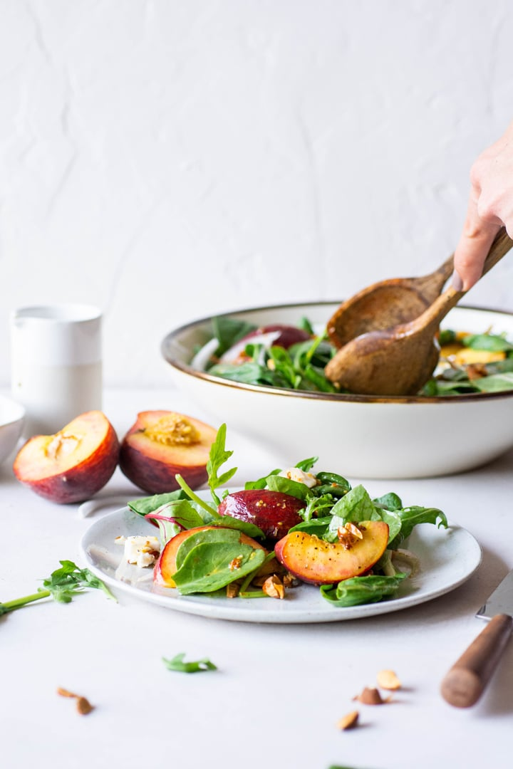Side view of someone dishing out some green salad onto a white plate on a white background next to some halved peaches and a fork and knife.