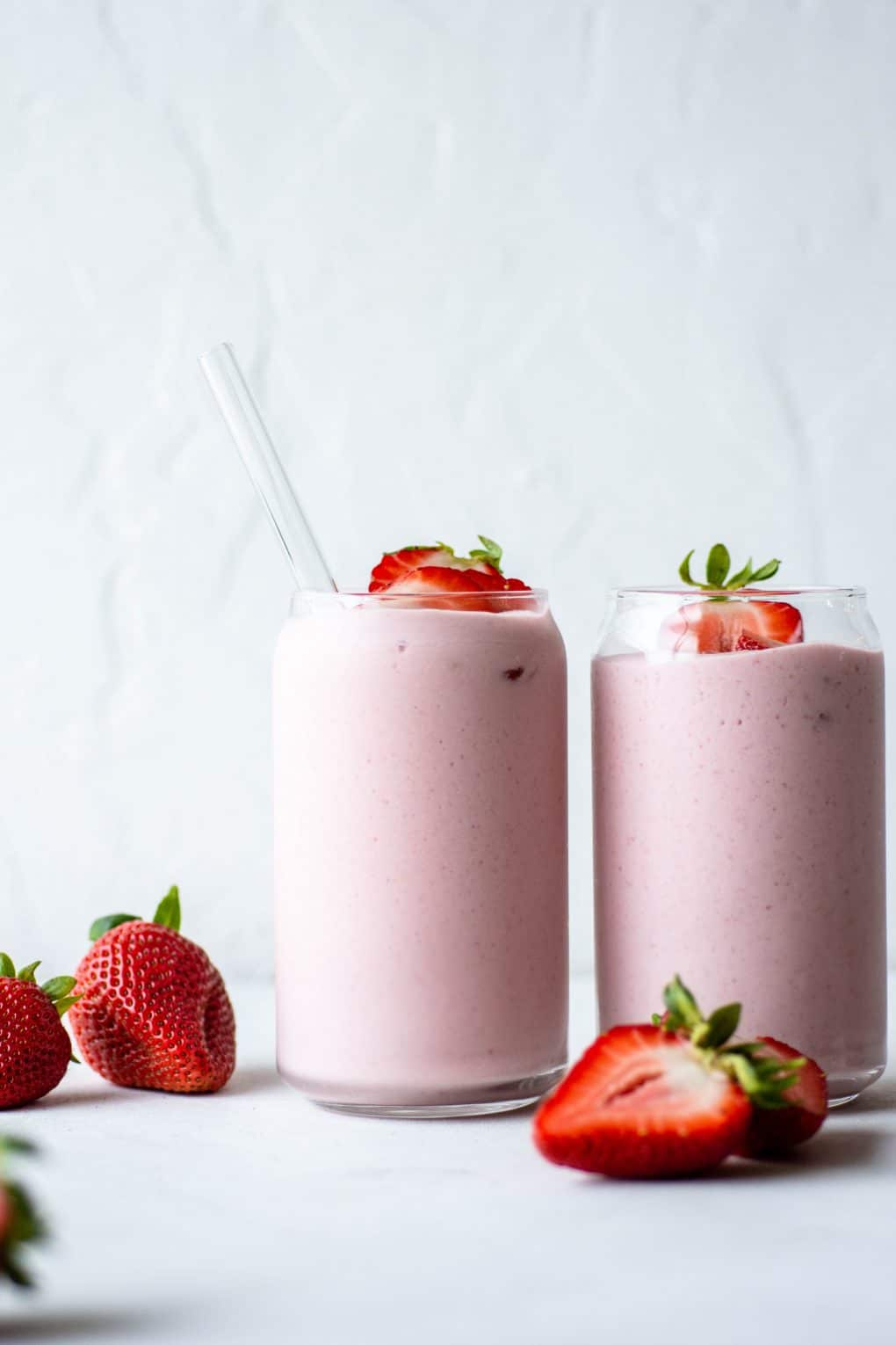 Close up view of two side by side pink strawberry milkshake from a clear glass jar into a cup surrounded by fresh strawberries on a white background